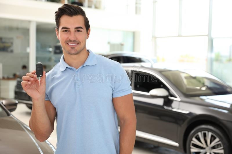 Happy young man with car key in  auto dealership. Space for text. Happy young man with car key in modern auto dealership. Space for text royalty free stock images