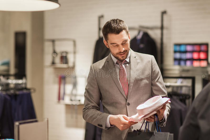 Happy young man choosing shirt in clothing store royalty free stock photography