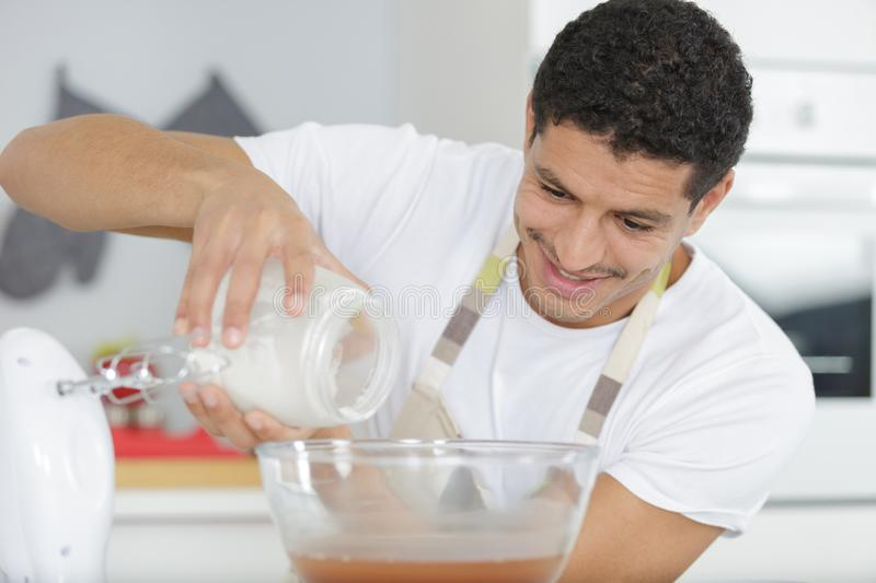 Happy young man cooking cake royalty free stock images