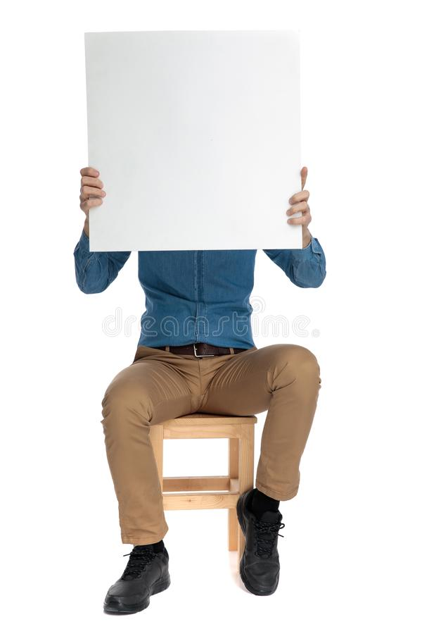 Happy young man covering face with empty board stock photo