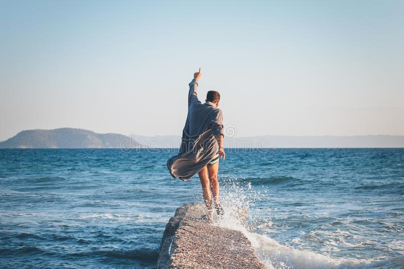 Happy young man dancing on the dock stock image