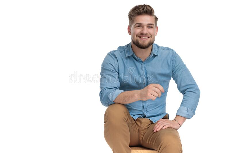 Happy young man in denim shirt smiling and holding elbow on knee royalty free stock photography