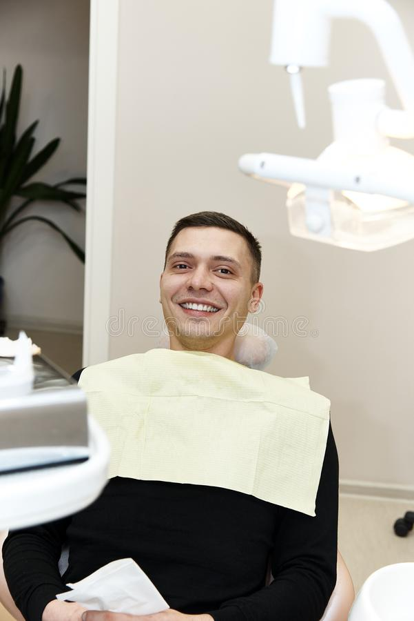 Happy young man in dental chair royalty free stock photography