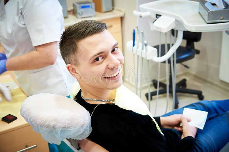 Happy young man in the dental office clinic stock photography