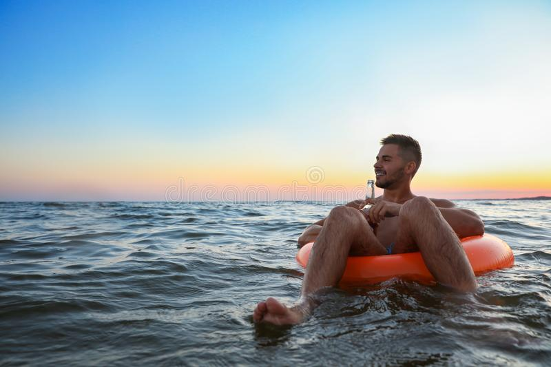 Happy young man with drink on inflatable ring stock photo