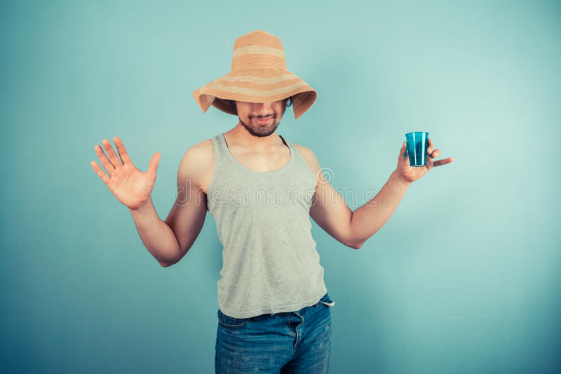 Happy young man drinking from blue cup stock image
