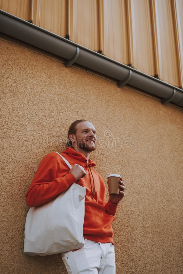 Happy young man drinking coffee on walk. Urban lifestyle concept. Waist up low angle portrait of young happy hipster man drinking coffee while leaning on stock images