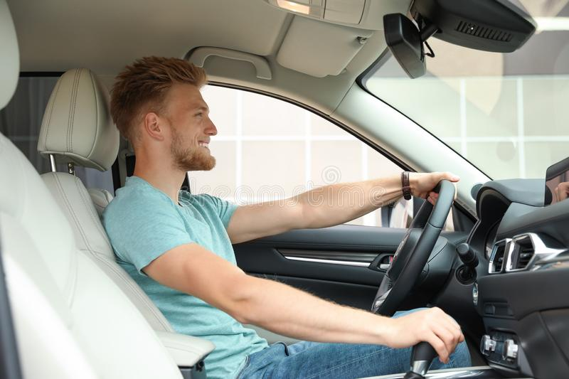 Happy young man driving his car stock photo