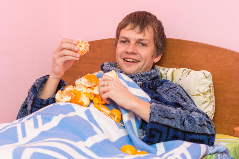 Happy young man eats tangerines stock photos