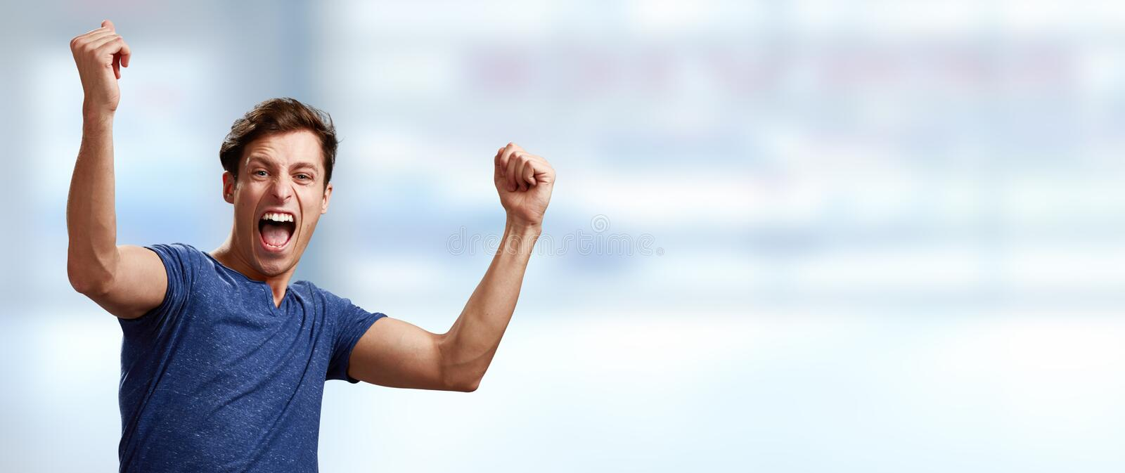 Happy young man. Happy excited laughing winner young man face expression stock photo
