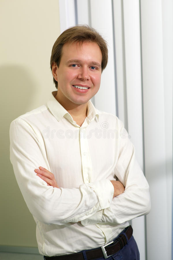 Happy young man with folded arms indoor. Portrait of a young smiling man posing with folded arms by the window with blinds royalty free stock photography