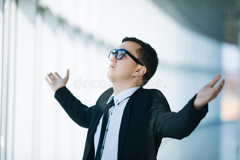 Happy young man in formalwear celebrating, gesturing, keeping arms raised and expressing positivity in panoramic window office stock photos