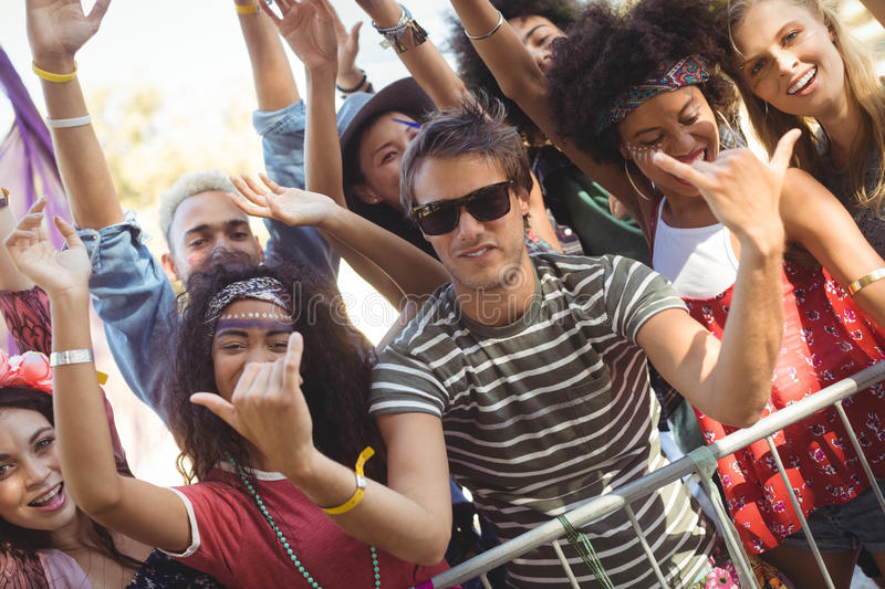 Happy young man gesturing shaka signs with friends at music festival stock images