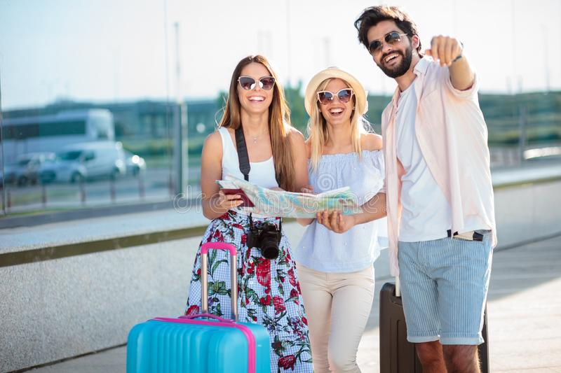 Happy young man giving directions to two female tourists, standing in front of an airport terminal building royalty free stock photography