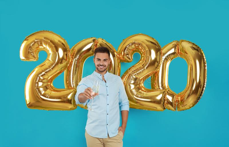 Happy young man with glass of champagne near golden 2020 balloons on turquoise background stock photos
