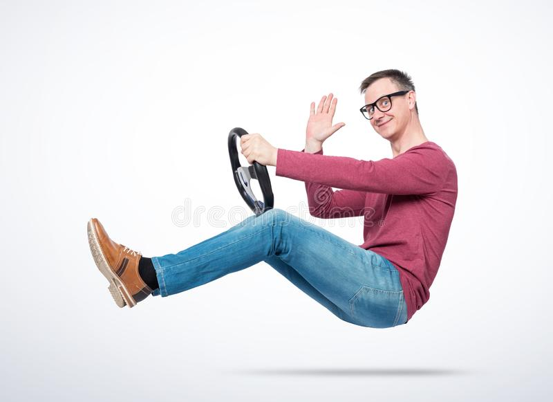 Happy young man in glasses driving a car sends greetings to the camera. Auto driver concept.  royalty free stock image