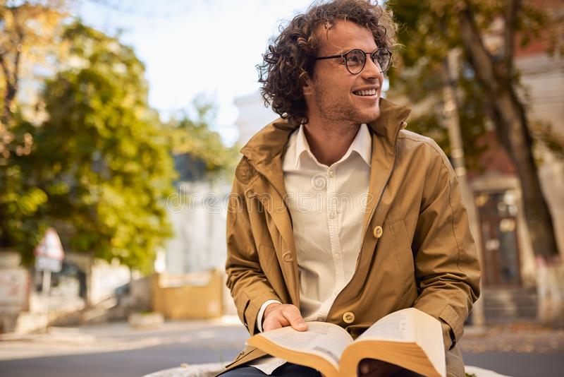 Happy young man with glasses reading and posing with book outdoors. College male student carrying books in campus in autumn street. Smiling guy wears royalty free stock image