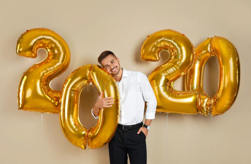 Happy young man with golden 2020 balloons on beige royalty free stock images