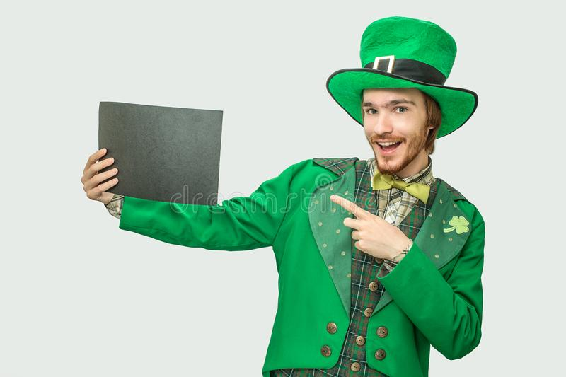 Happy young man in green suit holding black piece of paper. He wears saint Patrick`s suit. on grey background. stock photo