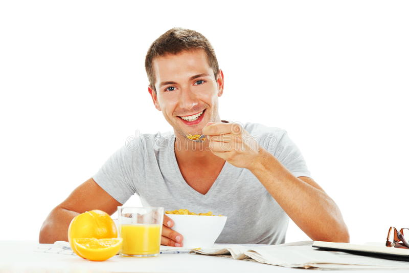 Happy young man having energetic breakfast. With white background royalty free stock photos