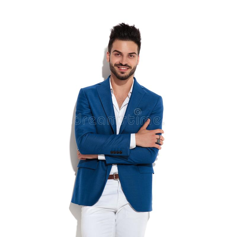 Happy young man having his arms folded around his chest. Happy young man looking at the camera and having his arms folded around his chest while wearing a blue royalty free stock photos
