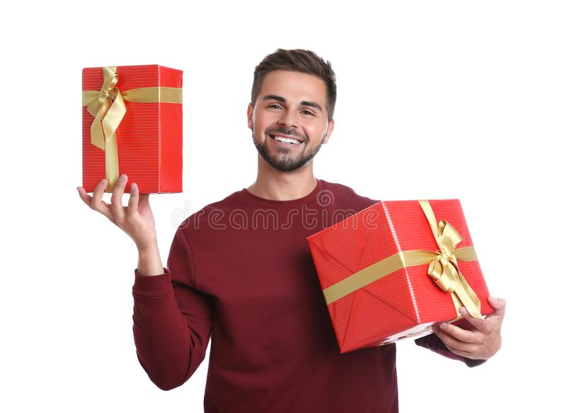 Happy young man holding Christmas gifts on background stock photos