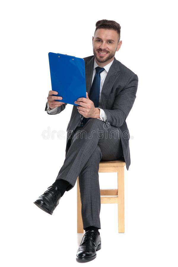 Happy young man holding clipboard and smiling royalty free stock photo