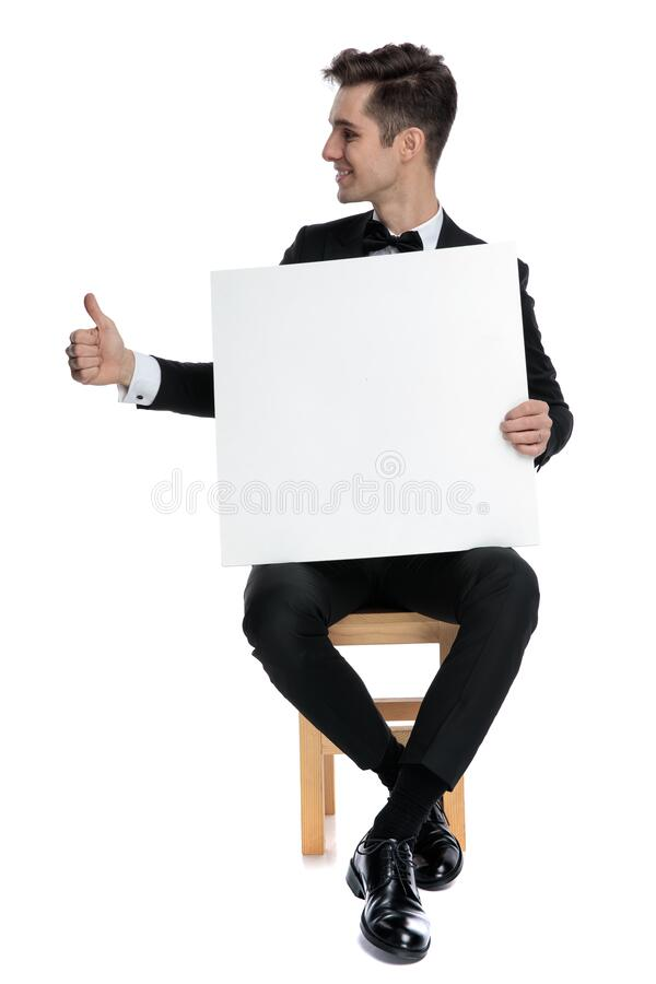 Happy young man holding empty board and making thumbs up sign royalty free stock images