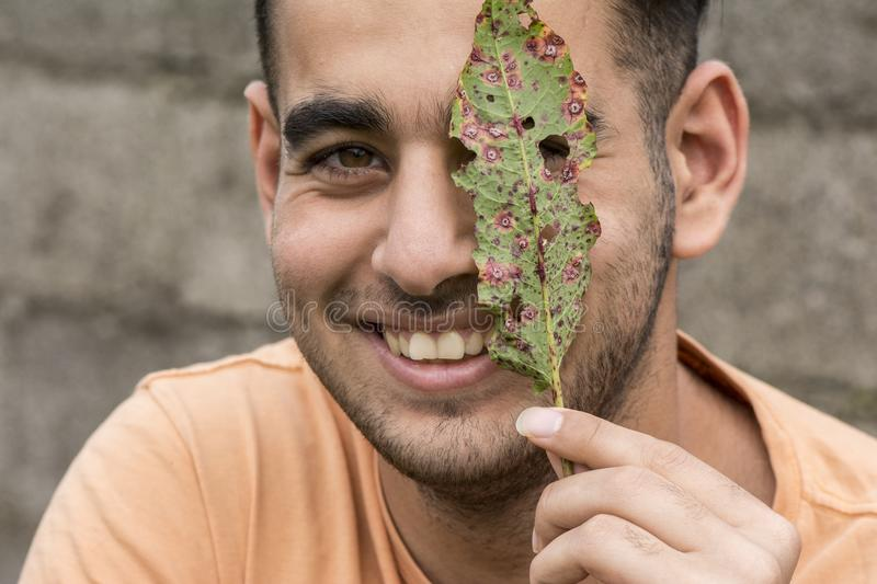 Happy young man holding a ruin leaf in front of face at outdoor royalty free stock photography