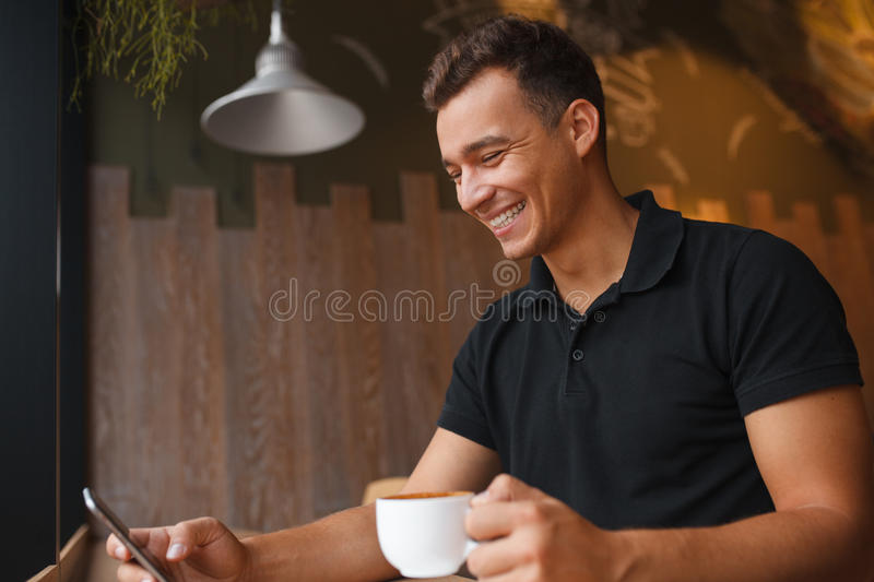 Happy young man holding smart phone and typing a message stock image