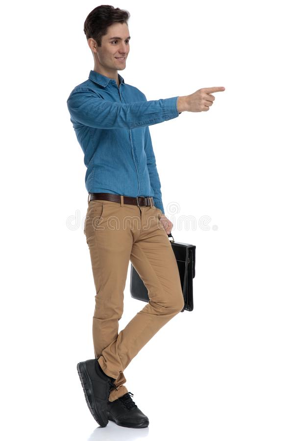 Happy young man holding suitcase and pointing finger royalty free stock images