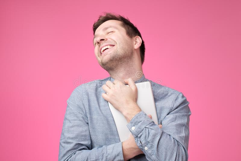 Happy young man holding tablet standing over pink wall stock image