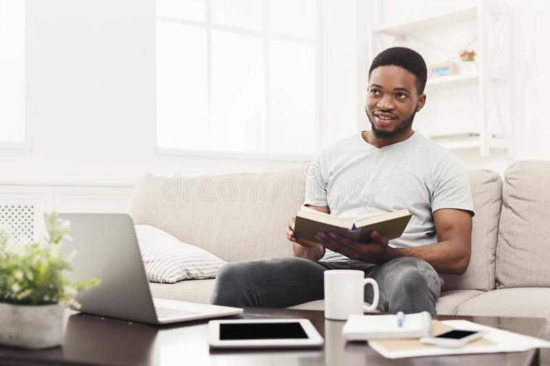 Happy young man at home reading book stock image
