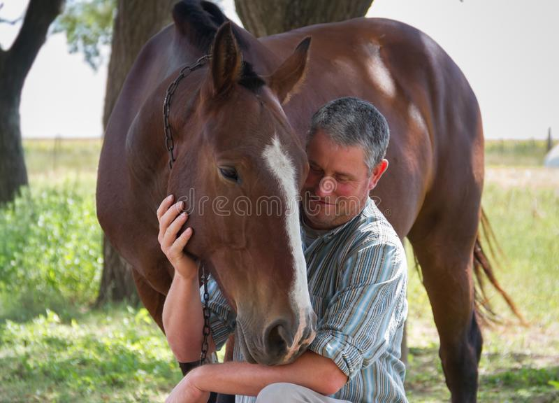 Smiling man with his horse in the Argentine countryside royalty free stock photos
