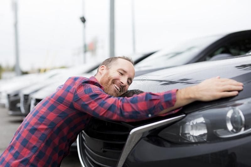 A Happy young man hugging his car outside of garage shop. Happy young man hugging his car outside of garage shop stock photo