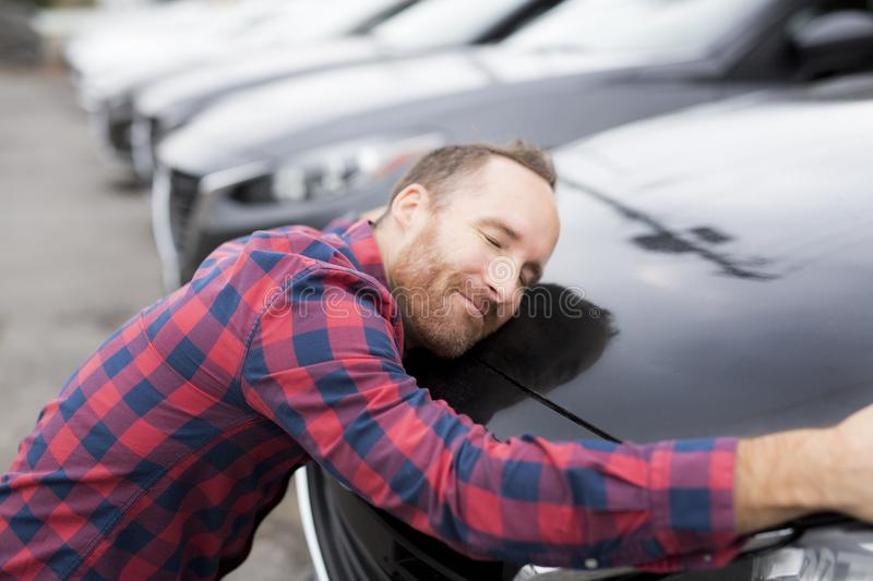 A Happy young man hugging his car outside of garage shop. Happy young man hugging his car outside of garage shop stock photography