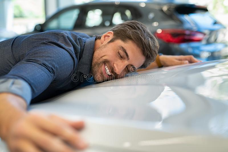 Young man hugging new car. Happy young man hugging his new car in showroom. Satisfied guy with closed eyes embracing the hood of the automobile. Dreaming man royalty free stock photo
