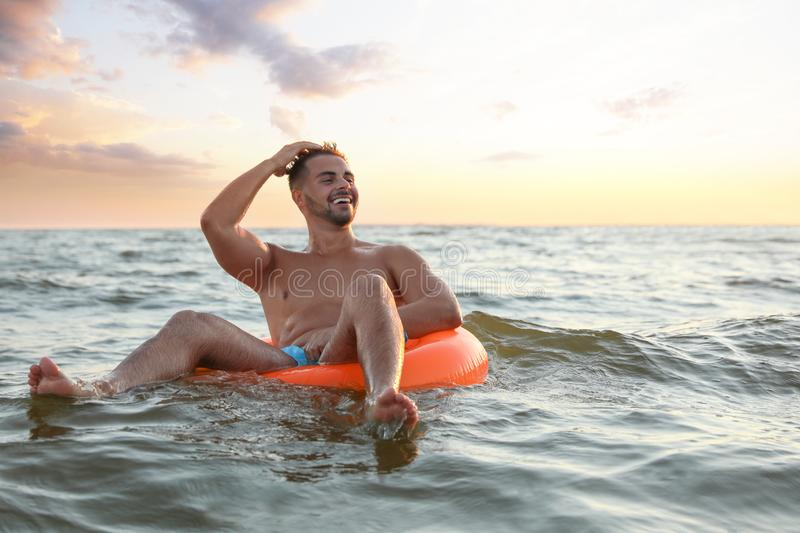Happy young man on inflatable ring stock photos