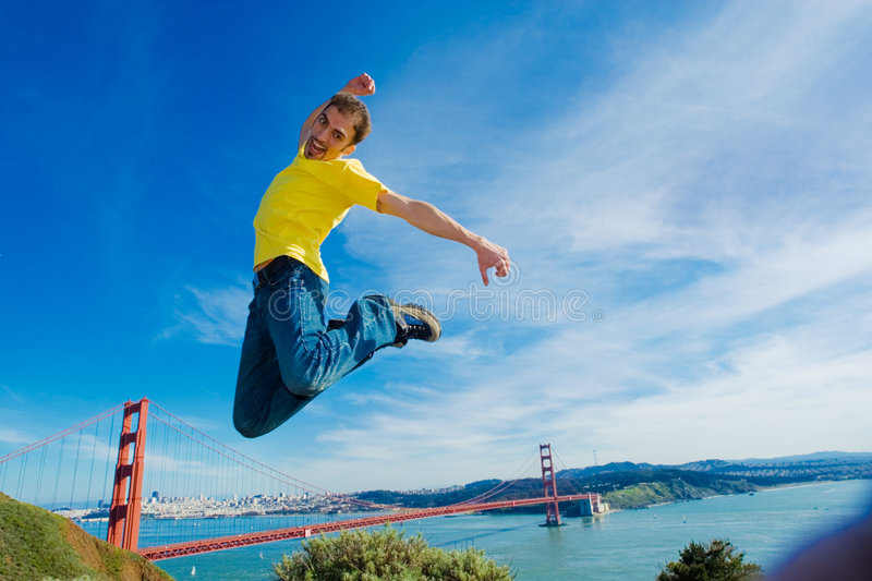 Happy young man jumping high in the air. Next to the Golden Gate bridge, San Francisco, California stock photography