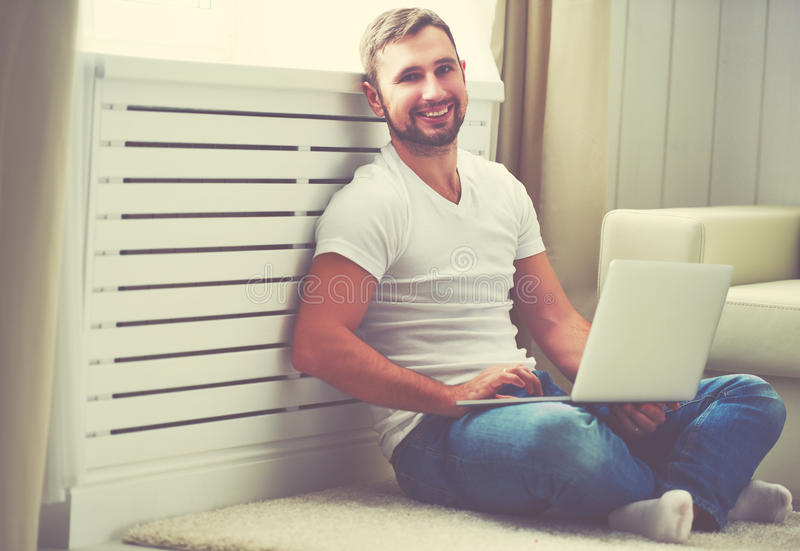 Happy young man with laptop computer at home. Happy young man with a laptop computer at home on floor near window stock photography
