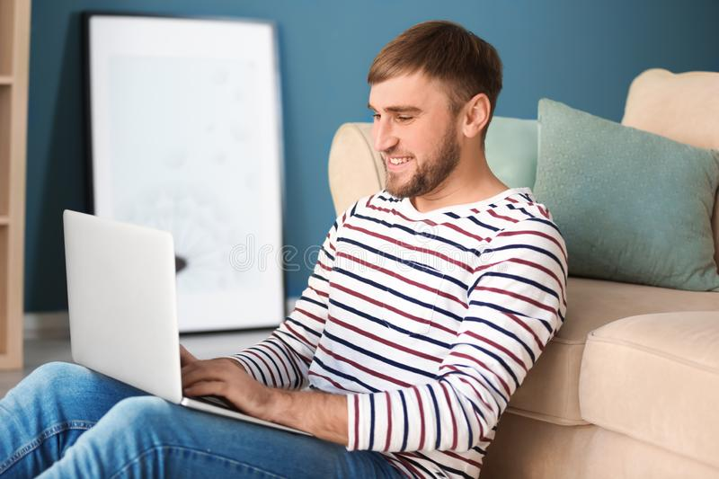 Happy young man with laptop at home stock photos