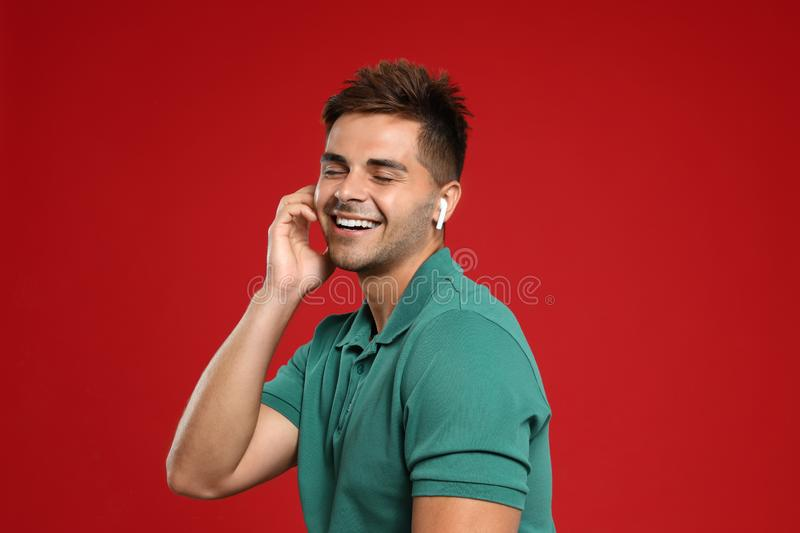 Happy young man listening to music through wireless earphones on background royalty free stock images
