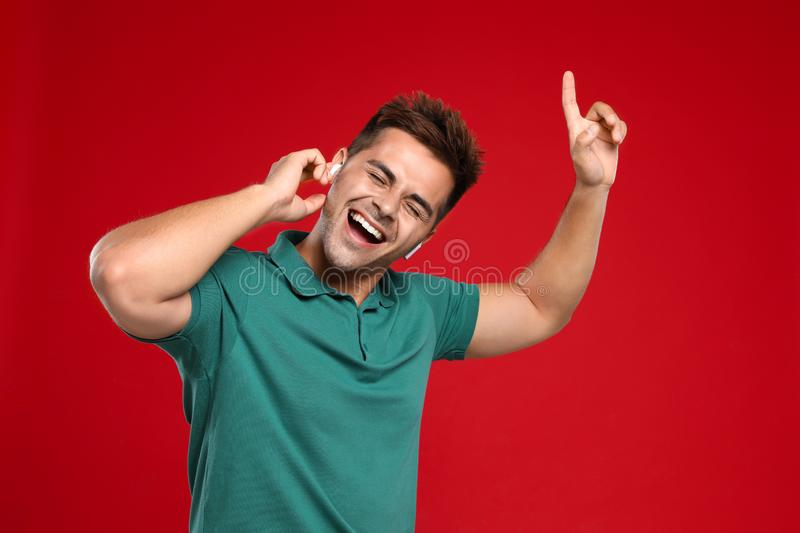 Happy young man listening to music through wireless earphones on background royalty free stock image