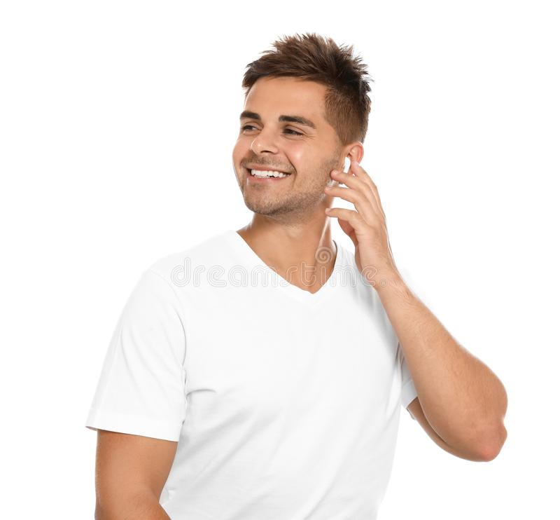 Happy young man listening to  through wireless earphones on white background stock images