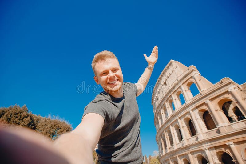 Happy young man making selfie in front of Colosseum in Rome, Italy. Concept travel trip stock images
