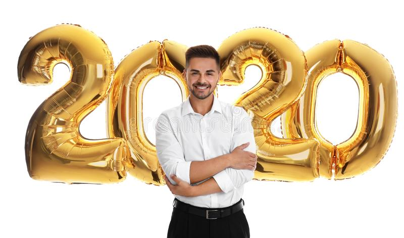 Happy young man near golden 2020 balloons on white. New Year celebration royalty free stock photos