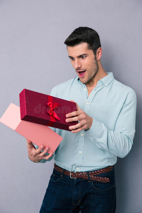 Happy young man opening gift box. Over gray backgorund royalty free stock images
