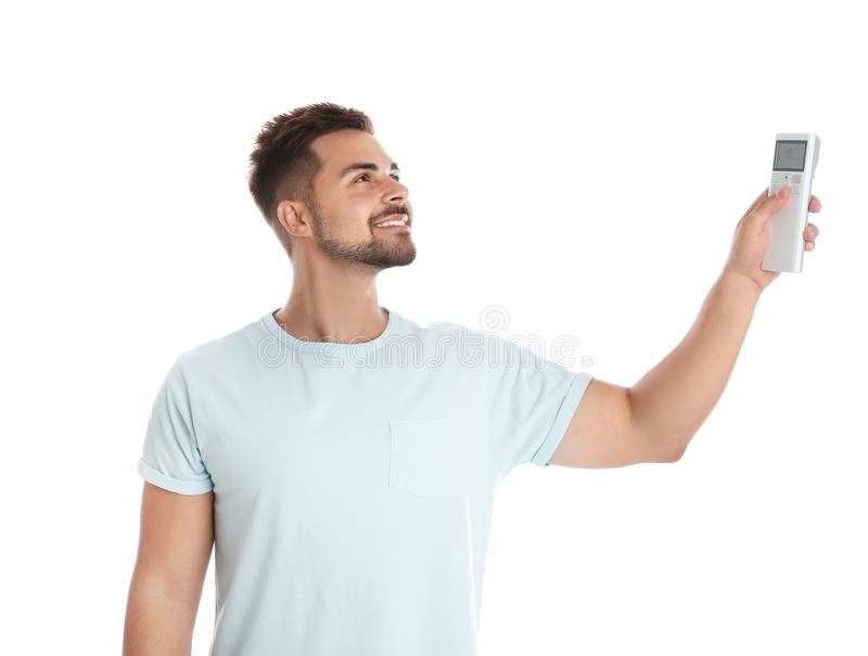 Happy young man operating air conditioner with remote control on white stock photos