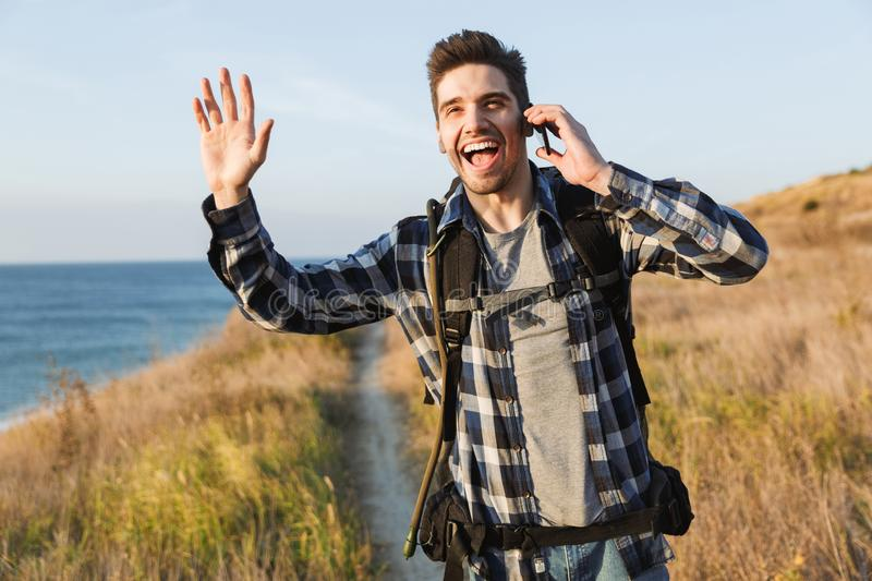 Happy young man outside in free alternative vacation camping talking by mobile phone royalty free stock photos