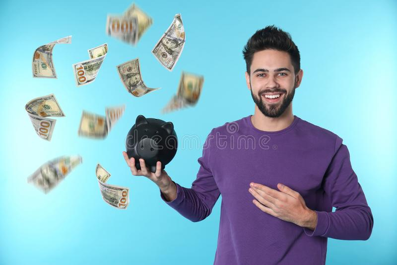 Happy young man with piggy bank on color background. Money saving stock photography